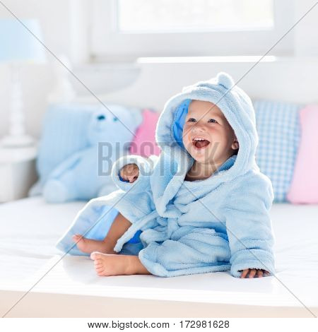 Cute happy laughing baby boy in soft bathrobe after bath playing on white bed with blue and pink pillows in sunny kids room. Child in clean and dry towel. Wash infant hygiene health and skin care.