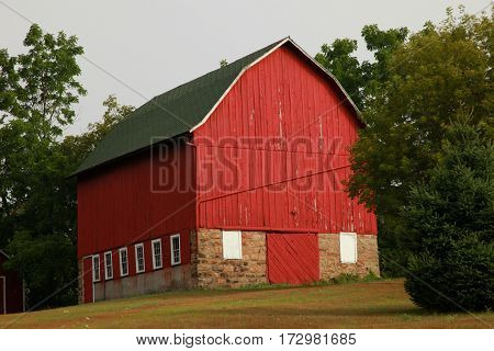 Red dairy barn standing alone on grassy slope