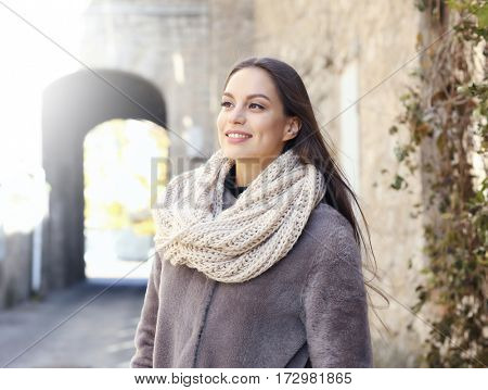 Beautiful young woman near old building on sunny autumn day