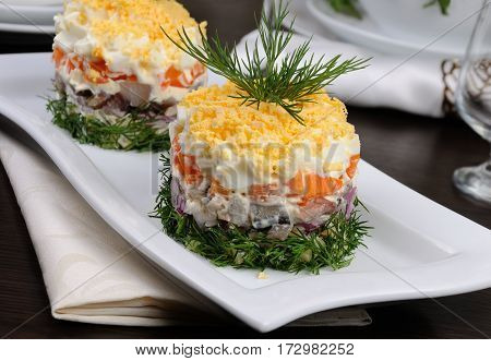 salad stacked chopped herring with potatoes carrots onions egg with mayonnaise strewn with grated egg yolk