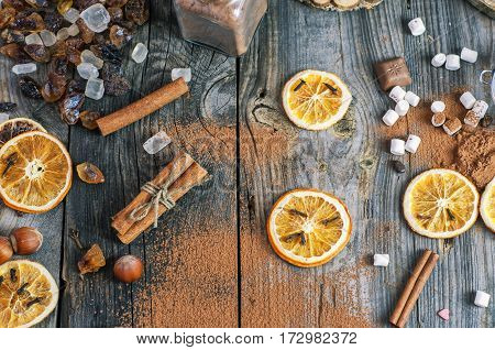 Dried slices of orange and cocoa powder on a gray wooden surface top view