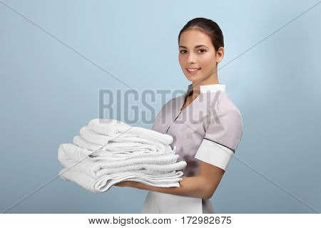 Female chambermaid  holding clean white folded towels on grey background