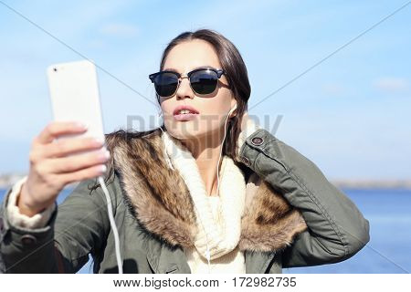 Beautiful young woman taking selfie at seashore on sunny autumn day, close up