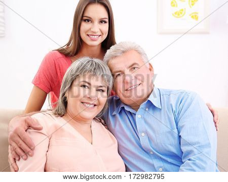 Young woman with middle aged parents on sofa in the room