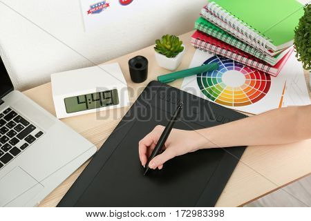 Young designer drawing sketches on graphic tablet