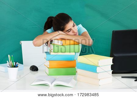 Close-up Of A Young Woman Resting On Pile Of Books In A Classroom