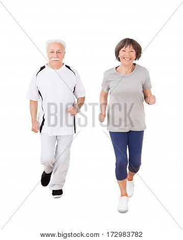 Portrait Of Senior Couple Jogging Over White Background