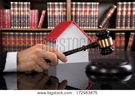 Judge In A Courtroom Striking The Gavel In Front Of House Model On Desk