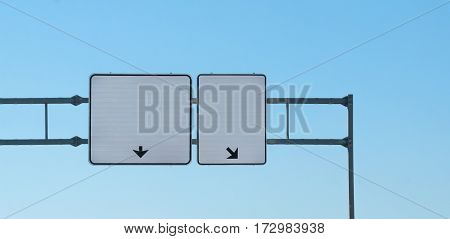 Two overhead blank highway signs, each has arrow pointing different direction, where to go, insert your text.  Copy-space, white-space