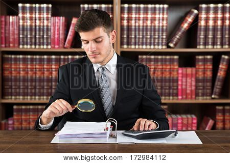 Male Lawyer Auditor Bills Using Magnifying Glass And Calculator