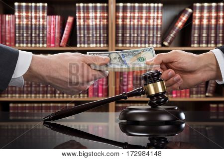 Close-up Of A Gavel On Table With Judge Taking Bribe From Client In Courtroom