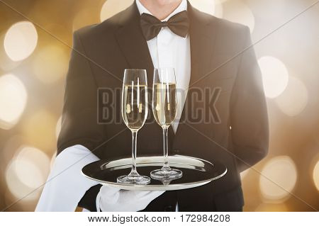 Close-up Of A Waiter Serving Glass Of Champagne In Tray