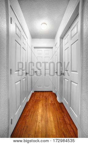 Vertical shot looking down a hallway with four doors and a wooden floor.