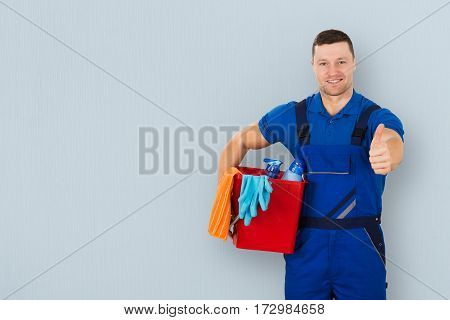 Portrait Of A Smiling Male Janitor Carrying Cleaning Equipment Showing Thumbs Up