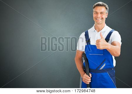 Portrait Of A Smiling Mid Adult Male Janitor Standing Against Gray Background