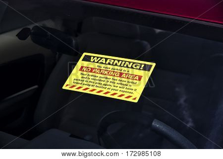 Horizontal shot of a warning sticker on a car windshield.