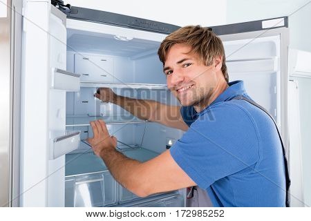 Male Technician Examining Broken Refrigerator Appliance At Home