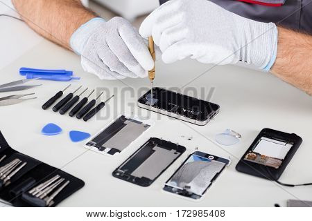 Close-up Of Person's Hand Wearing Glove Repairing Cellphone Using Screwdriver