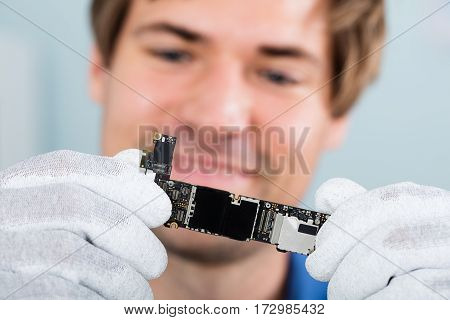 Close-up Of A Happy Man Holding Smart Phone Circuit Board Wearing Glove
