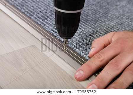 Person's Hand Installing Carpet On Floor Using Wireless Screwdriver