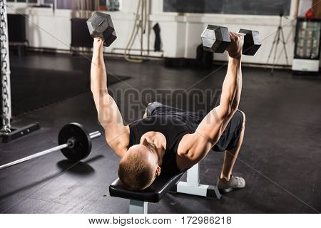 Young Man Doing Dumbbell Fly On Bench In The Gym