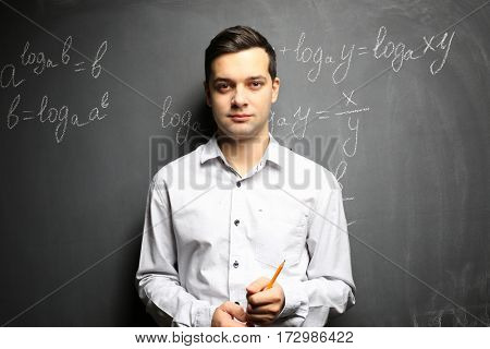 Handsome young teacher standing near blackboard