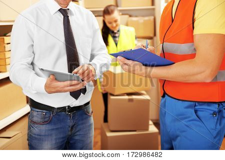 Two young businessmen working at warehouse