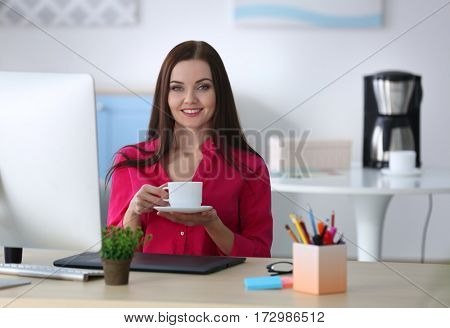 Young beautiful designer drinking coffee in office