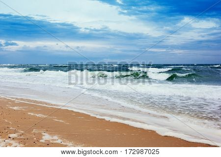 coastline with yellow sand, green sea and  blue sky