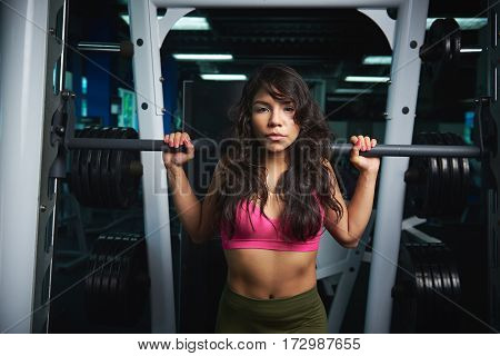 Sporty woman lifting barbell on fitness club background. Girl doing squat with barbell