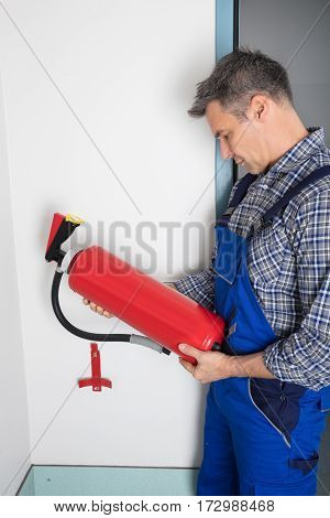 Male Professional Checking The Condition Of A Fire Extinguisher