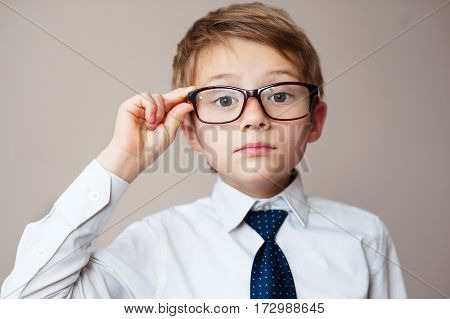 Portrait of schoolboy with glasses on white background