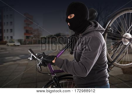 Thief Wearing Balaclava Stealing A Cycle On Street