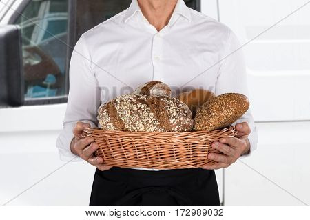 Close-up Of A Baker Holding A Basket Full Of Bread Loaf In Front Of Van