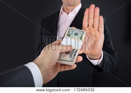 Close-up Of A Businessman Hand Refusing To Take Bribe On Black Background