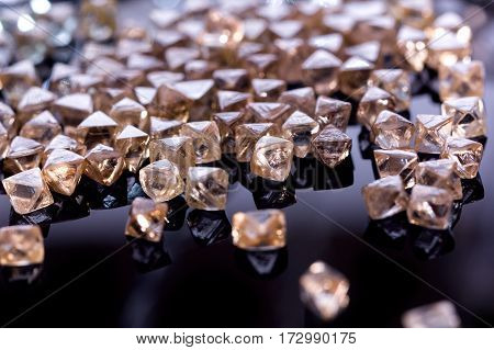 Collection of faceted natural transparent diamonds in macro with yellow reflection in the black background