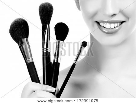 Female with cosmetic brushes, white background, copyspace