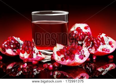 pieces of red pomegranate and pomegranate juice on a black background with red lighting