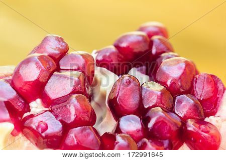 piece of red pomegranate in macro on the yellow background