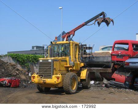A Truck Lifting A Car Wreck Into Press