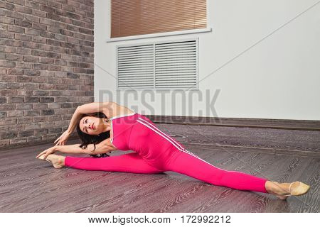 Full length portrait of young cuacasian ballet dancer practicing indoors. Sporty woman warming up and stretching at fitness class