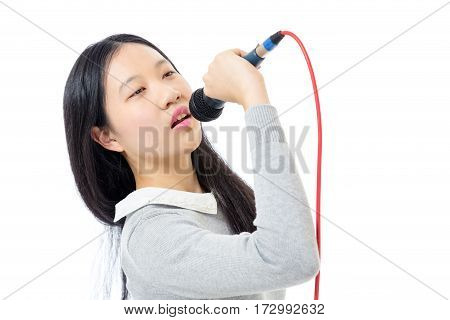 Chinese teenage girl holding microphone and singing