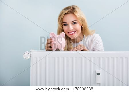 Young Happy Woman With Piggybank On Radiator At Home