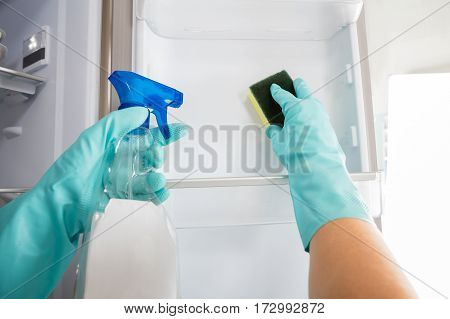 Close-up Of Person Hand Cleaning Refrigerator With Spray Bottle And Sponge