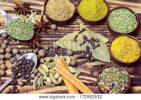 various spices in containers, in spoons and on a wooden background