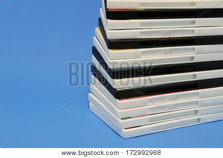 stacking DVD movie boxes on blue background