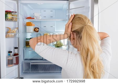 Rear View Of A Confused Woman Looking Inside The Fridge