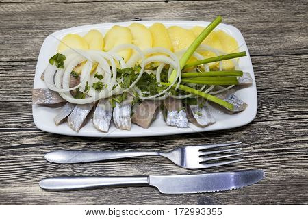 Tasty pieces of Icelandic herring with boiled potatoes and onions on the plate. National Icelandic snack Fat herring.