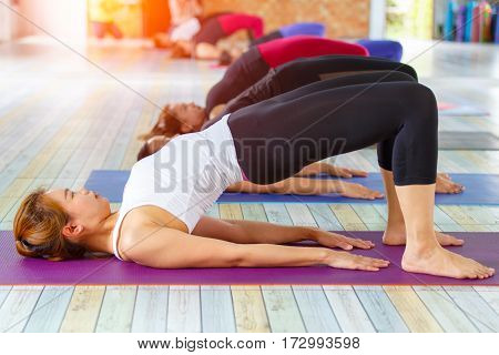 Fitness asian female group doing namaste yoga pose in row at the yoga class. selective focus