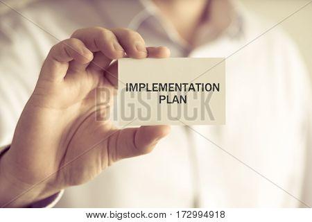 Businessman Holding Implementation Plan Message Card